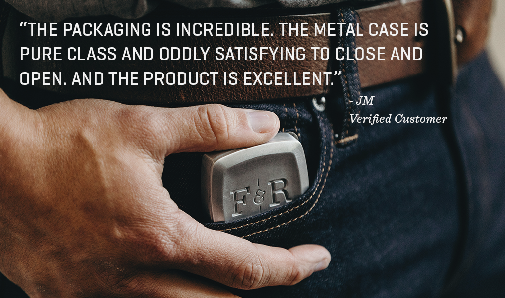 "Image of a hand putting cologne in pocket with quote: ""THE PACKAGING IS INCREDIBLE. THE METAL CASE IS  PURE CLASS AND ODDLY SATISFYING TO CLOSE AND OPEN. AND THE PRODUCT IS EXCELLENT."""