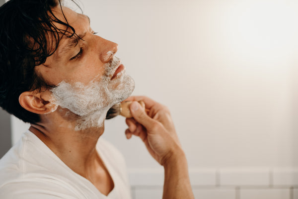 Image of a model applying shave cream on his face with a shave brush