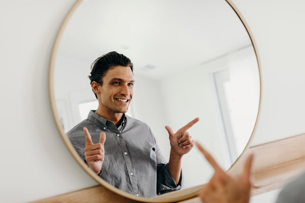 Image of model smiling and doing finger guns in front of the mirror