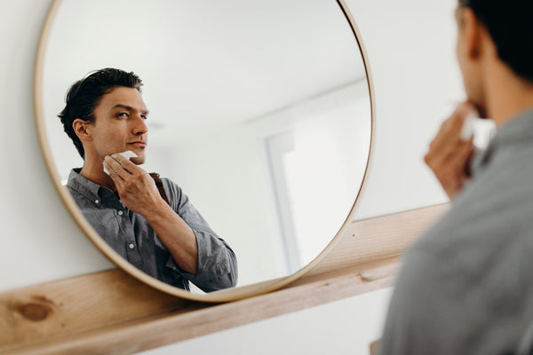Image of a model looking at a mirror while using aftershave cloths on his face