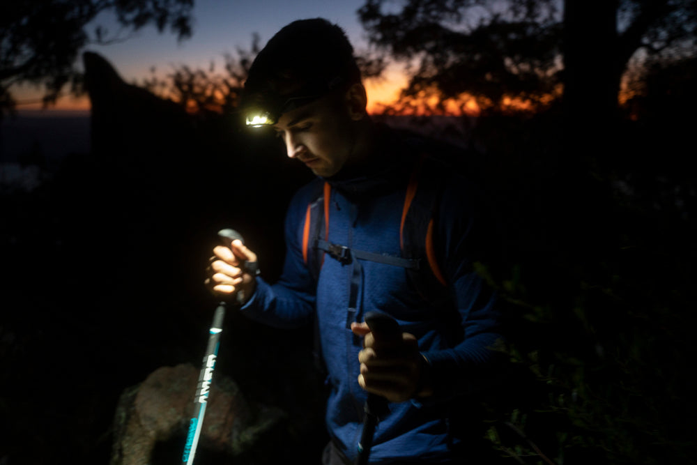 Trekking poles and head torch are helpful when walking down in the dark