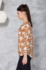 side view of a woman in a long sleeve peasant blouse in ahimsa silk with hand block print