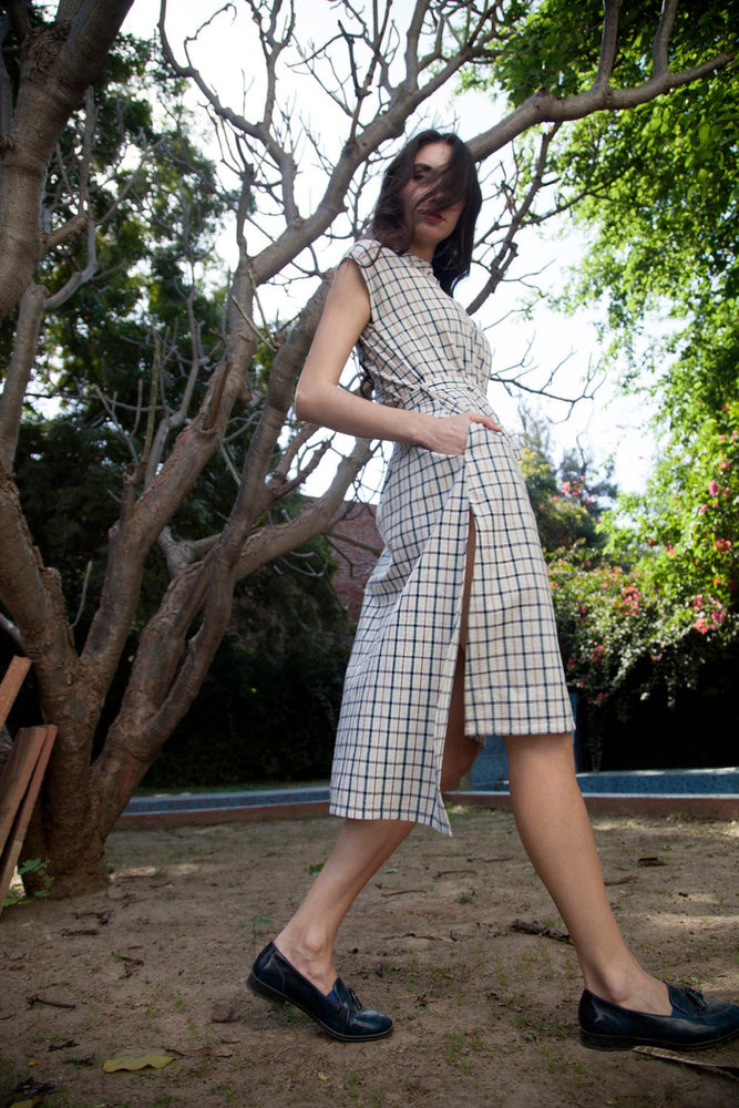 woman in a garden wearing a sleeveless ivory khadi checks tunic shirt dress with tie up belt