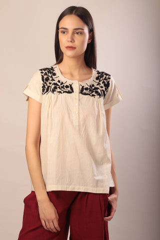 woman wearing an embroidered ivory and black khadi top