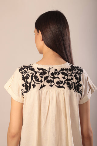 back of a woman wearing an embroidered ivory and black khadi top