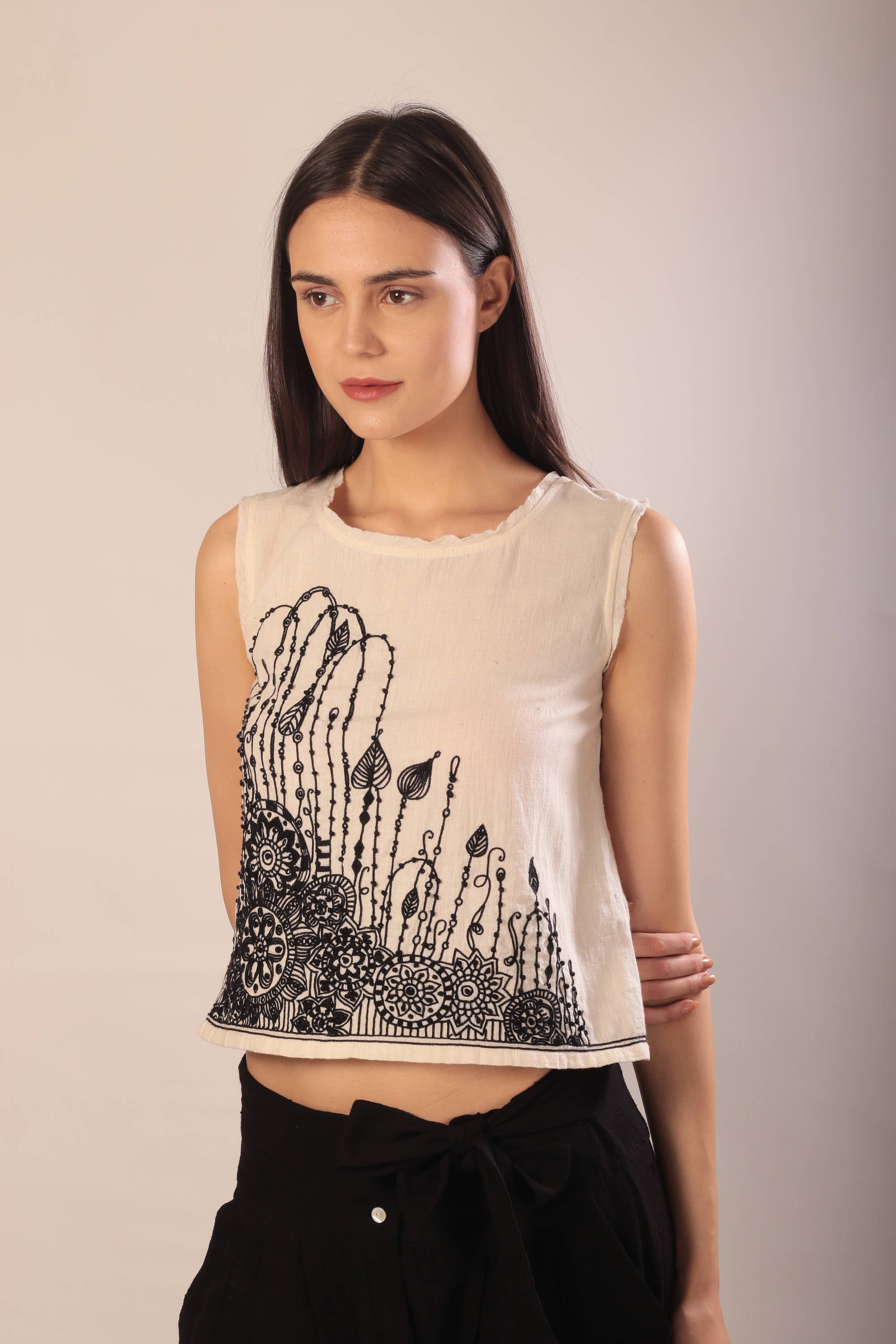 woman in a sleeveless ivory khaki tank top with black embroidery and black khadi pants