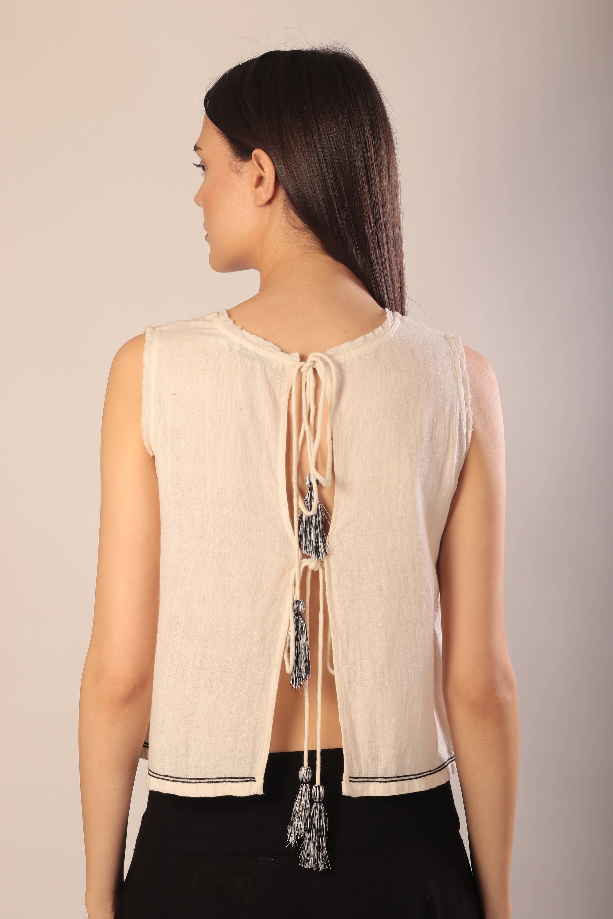 back view of a woman in a sleeveless ivory khaki tank top with tasseled tie ups and black khadi pants