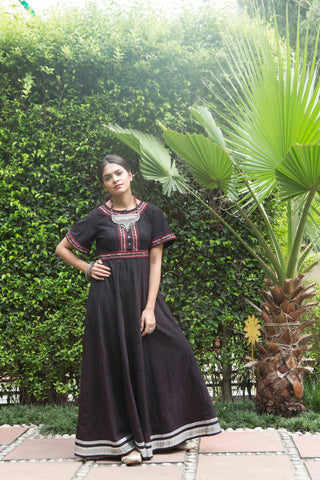 woman in a garden wearing short sleeve black maxi dress in khadi with metallic and mirror hand embroidery