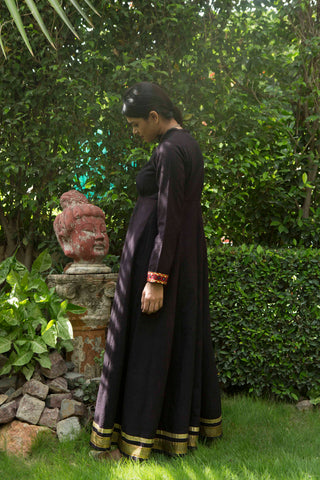 back of woman in a garden wearing long sleeve black khadi maxi dress with metallic embroidery