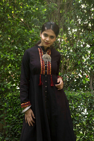 woman in a  garden wearing long sleeve black khadi maxi dress with metallic embroidery