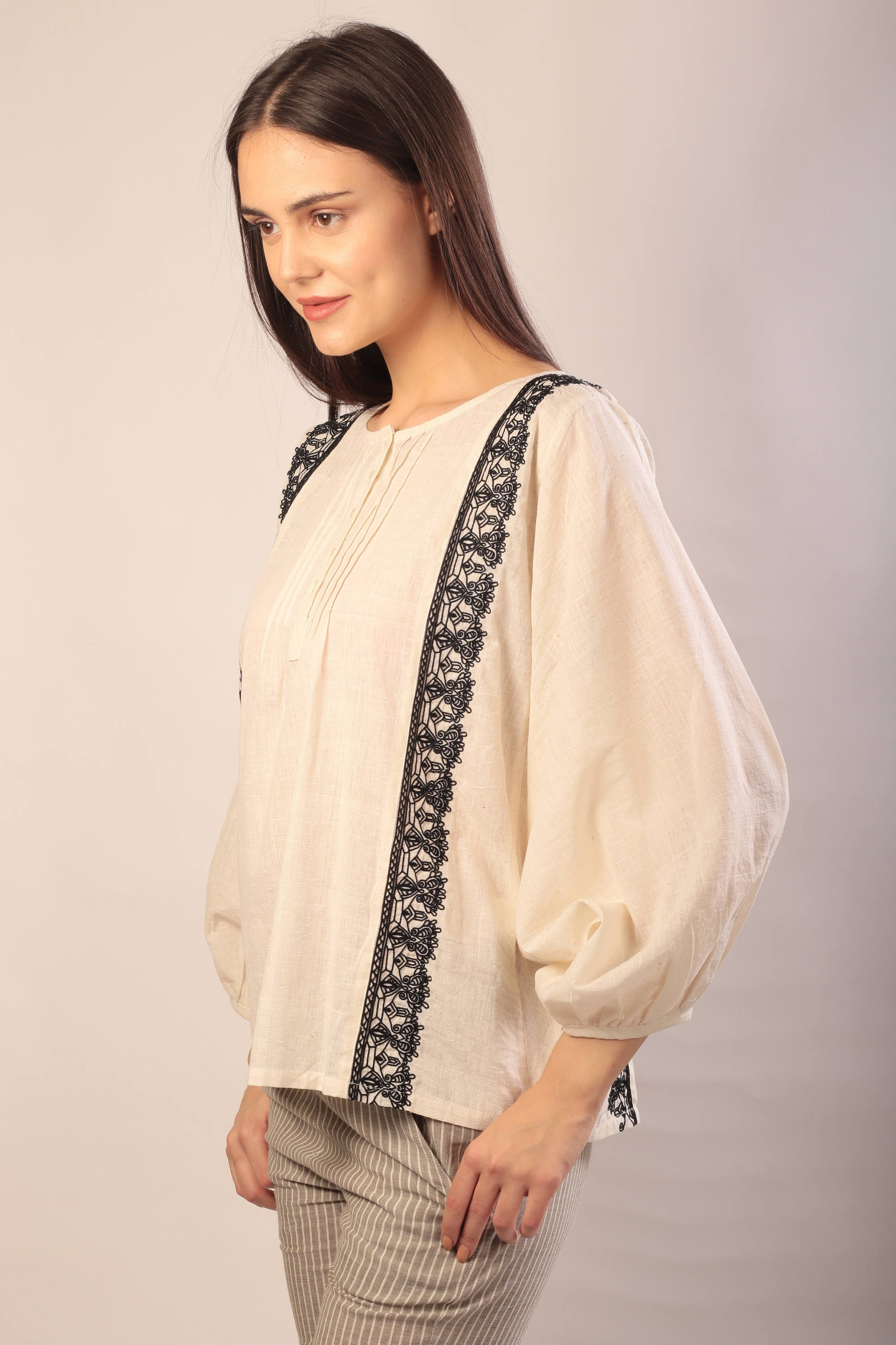 side view of woman standing in an ivory khadi long sleeve blouse with black hand embroidery