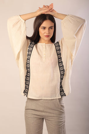 woman standing in an ivory khadi long sleeve blouse with black hand embroidery