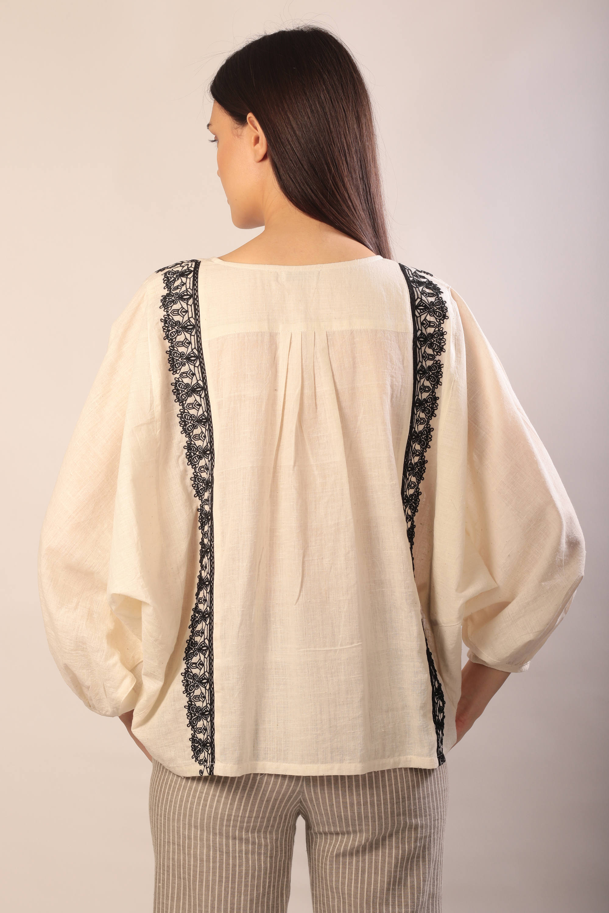back view of a woman standing in an ivory khadi long sleeve blouse with black hand embroidery