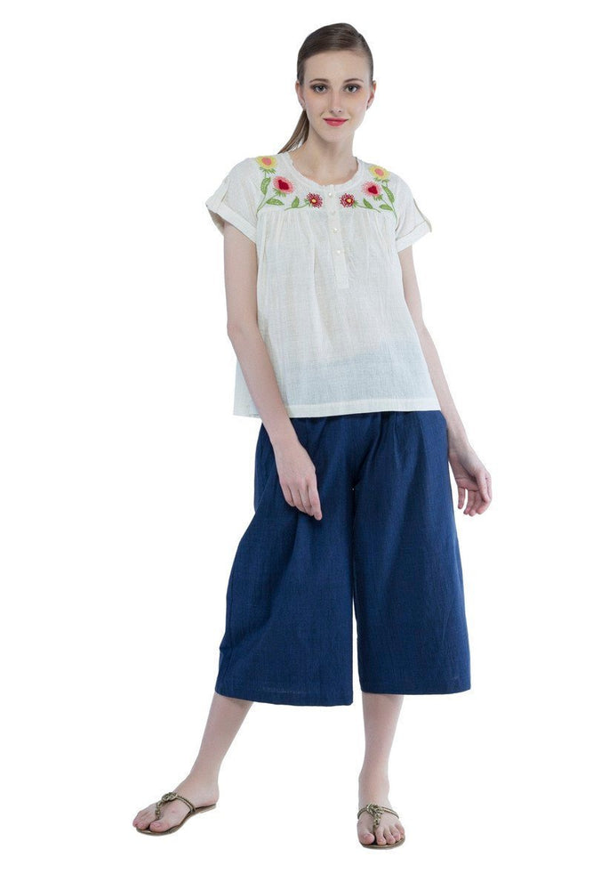 woman wearing white khadi top with floral embroidery and Indigo khadi wide leg pants