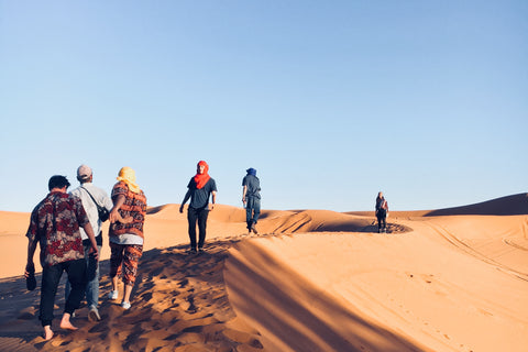 six friends are adventuring into the desert. Merzouga, Morocco. The are walking in a line on top of the dunes, the sky is bright blue and the sand is yellowish orange. They are all wearing bright colours and patterns and very bright Berber headscarves