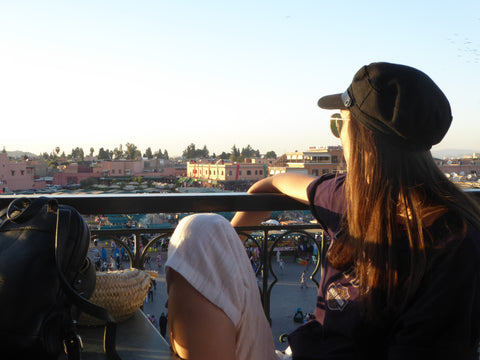 A girl sits on a roof terrace eating lunch in Marrakech on top of Jemaa el Fnaa