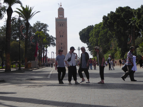 A group of young boys standing in amongst a crowd of people in front of the famous Koutoubia Mosque in Marrakech, Morocco. One of the boys is wearing a vegetable tanned moroccan leather bumbag