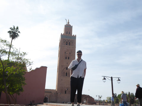 A boy stands in the largest square in Africa, he is in front of Koutoubia Mosque in Marrakech and he is wearing a hat, a white shirt and a vegetable tanned Moroccan leather bag