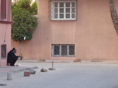 The streets of Gueliz a man sits and eats his lunch on a corner, he is in Marrakech Morocco and the walls are completely painted pink