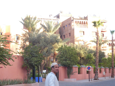A local man in Gueliz, Marrakech Morocco. He walks in the city and is surrounded by pink walls and lush trees