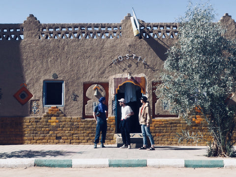 Three people stand outside the local hostel in Merzouga, Morocco. The weather is hot and the sky is blue