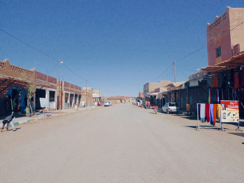 The main street in Merzouga, Morocco. A small town located in the middle of the Moroccan desert. The road is dusty
