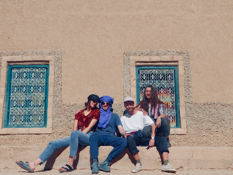Four young people boys and girls sit in front of a local building in Merzouga Morocco, the windows have traditional Moroccan metal work on them. they are wearing brightly coloured pattern shirts and traditional Berber headscarf to protect their face from the wind and the sand