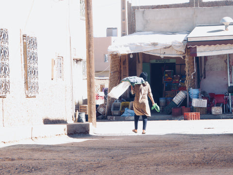In the streets of Merzouga a woman carries a big bag of goods into the main street, she is wearing a hijab