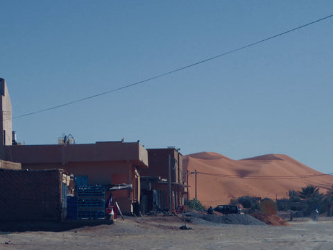 A picture taken from the town peering into the Desert. You can see a small dune it is orange in colour, some building cover it slightly. The Desert is close