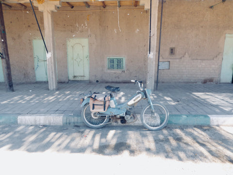 A motorbike stands alone in front of an old shop in Merzouga Morocco. The shop is closed it is hot and dusty