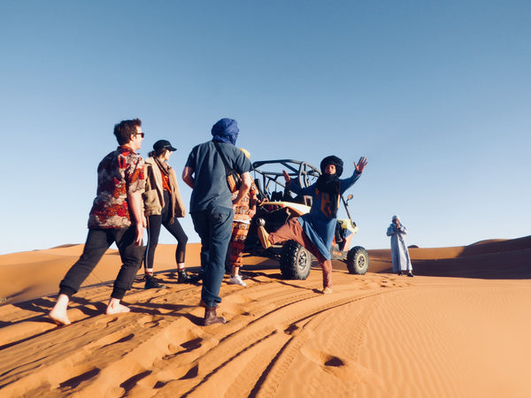 friends adventuring on a buggy in the western sahara