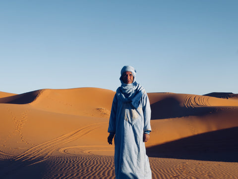A local berber man stands in the middle of the Sahara desert. He is in Merzouga Morocco he is wearing a full berber outfit and head scarf dyed in the traditional indigo blue. He is surrounded by nothing but orange sand and blue skies