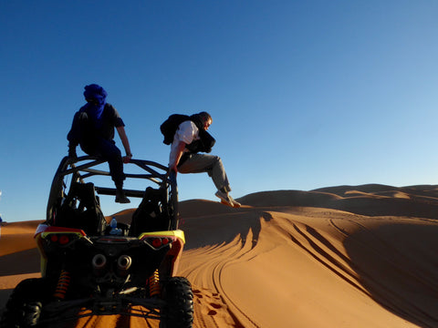 Two men are in the desert the are jumping off their dune buggy. They are in Merzouga Morocco. The sand is orange and the sky is blue