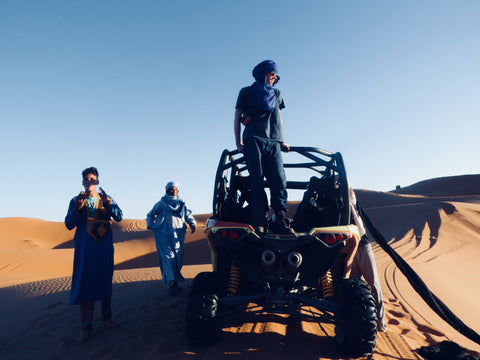 A man stands on his dune buggy in the Sahara desert. The sky is blue and the sand is orange. He is in Merzouga Morocca and by the buggy are two berber men, completely dressed in traditional outfits their suits are dyed blue with indigo