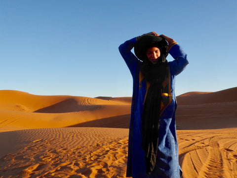 A berber man stands in the desert putting his black headscarf on his head, he is dressed in a traditional indigo jilaba.