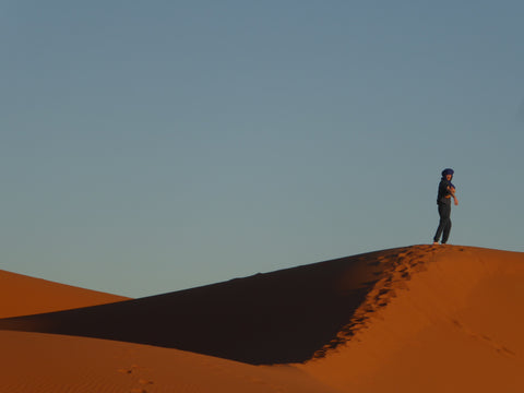 A young boy stands on top of the desert dunes, it is just him and the blue sky and the orange sand. HE is wearing a traditional Berber headscarf to protect his face from the sand and the wind