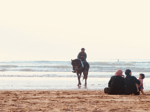 On the atlantic coast in Essaouira Morocco a family of locals sit on the beach watching the sunset. They're sitting on the sand and another Moroccan man rides past them on a horse, half in and half out of the water