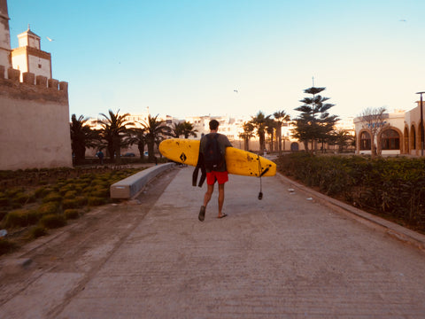 A expat travelling essaouira Morocco carries his surfboard from the atlantic coast back into the ancient medina. The path he walks has palm trees either side and the sun sets behind him