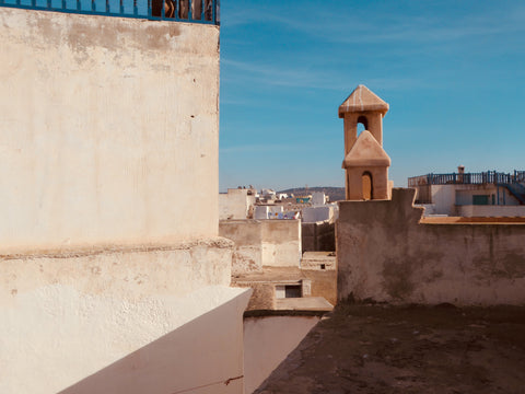 The view from a rooftop in Essaouira Morocco. You can see multiple terraces and the sun is out and the sky is blue