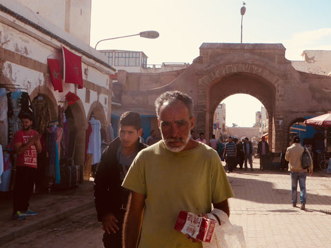 A local Moroccan man who is holding a carton of malbro cigarettes, he is walking through the local Medina with shops and people all around him, he is wearing a green t-shirt