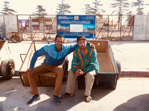 two local med who sit on their trailers outside the Medina pose for a photo, they are happy characters, with arm slung around the other they wait on this warm day in Essaouira for someone to need them to help carry goods around the old town