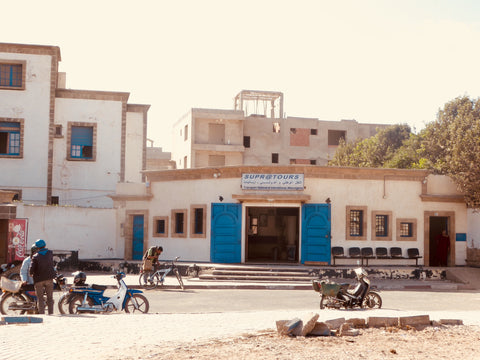 The local supratours bus station in Essaouira Morocco, with the locals hanging out front on their motorbikes.