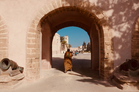A local Moroccan man walking into the old town through the city doors, the floor is dusty, it's a hot day and the sky is blue