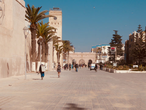 Essaouira Morocco, a picture of the local square in the median, with people wandering around, the sun is shining and the sky is blue