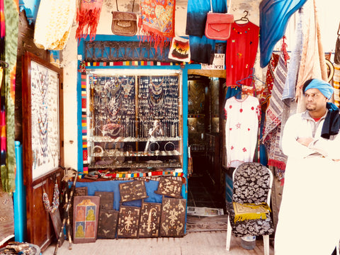 the local berber jeweller stands outside his vibrant shop in Essaouira Morocco. The shop is littered with jewels,hanging from every place possible