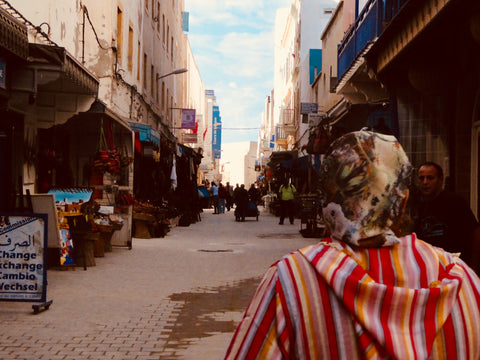 A local woman walks the streets of Essaouira Morocco, she wear a jalaba and there are local shops filing the streets on either side of her