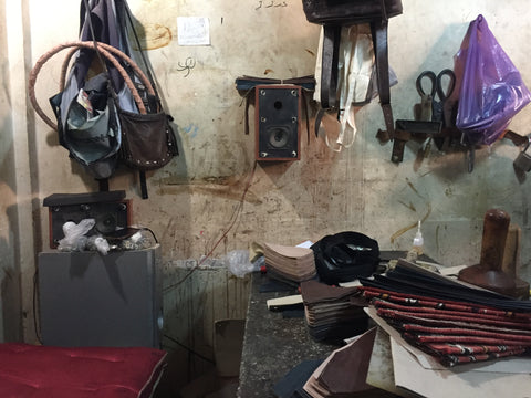 Inside the workshop where Moroccan leather artisan produces vegetable tanned Moroccan leather bags, there is a sewing machine and a small collection of leather and kilim carpet samples