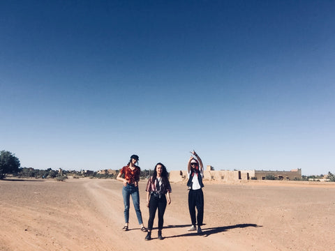 We found the nothingness and discovered it was everything. Three young adults stand on the edge of the desert in Merzouga Morocco. It is hot and dry, they are wearing red, pattern and brightly coloured shirts