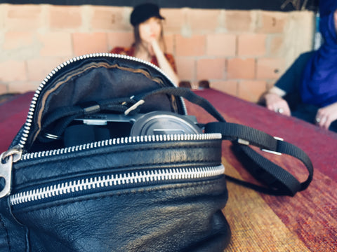 A vegetable tanned Moroccan leather bumbag sitting on a table in Merzouga Morocco. There is a digital camera in the bag