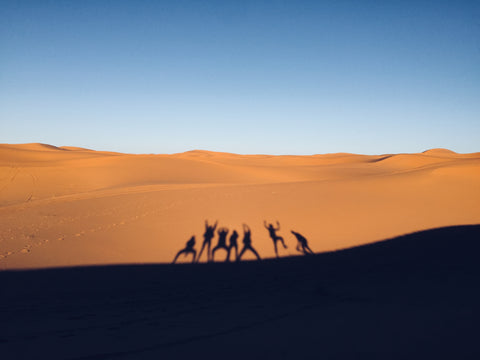 7 friends take a picture of their reflection in the desert. Merzozuga Morocco. The desert sand is bright orange and the sky is blue. They are all making shapes with their bodies